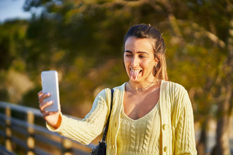 Portrait of smiling young woman using mobile phone outdoors
