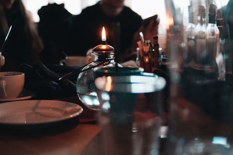 Close-up of lit candle by place setting on table in restaurant