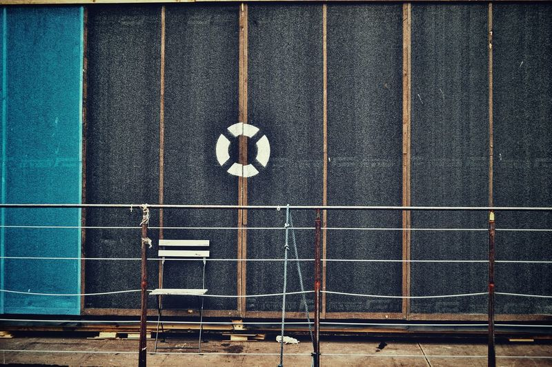 Empty chair against lifebelt symbol on wall