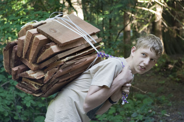 Teenage Boy Carrying Firewood In Forest