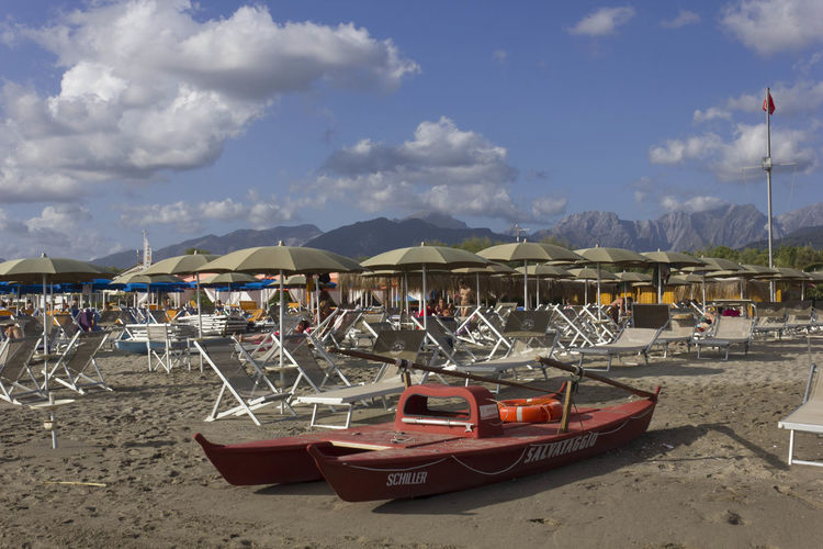 Bathing establishment in Marina di Massa Alps Italy Lifeboat Marina Di Massa Rowboat Tuscany Alps Bathing Establishment Beach Beach Day Beach Umbrella Day Italy Land Lifesaver Lounge Chair Outdoors Parasol Sand Shore Summer Sun Umbrella Versilia