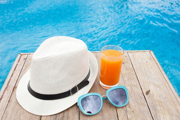 Close-up Day Drinking Glass High Angle View No People Outdoors Relaxation Summer Sun Hat Sunglasses Swimming Pool Vacations Water Wood - Material