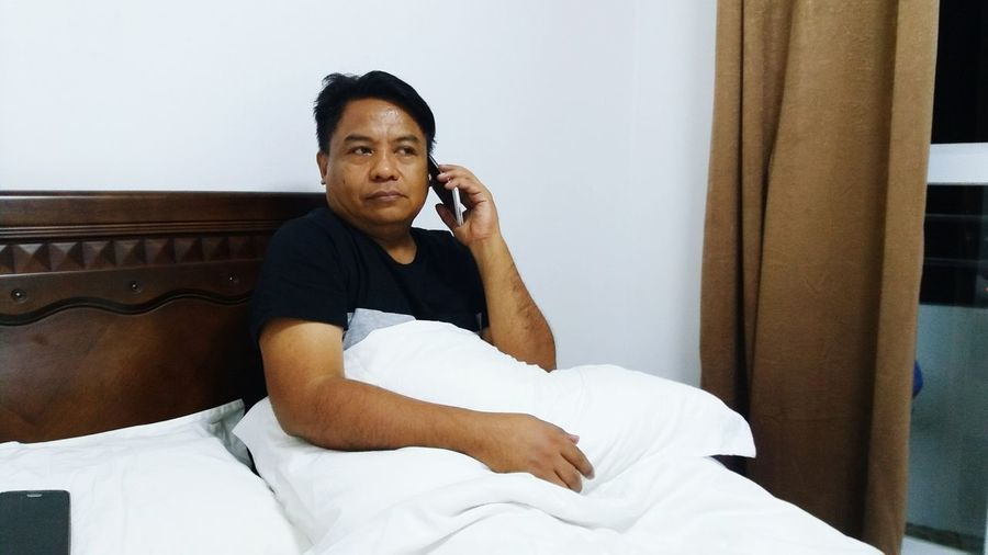 Man Talking On Phone While Relaxing On Bed At Home