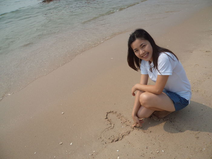 Portrait of smiling woman making heart shape while crouching at beach