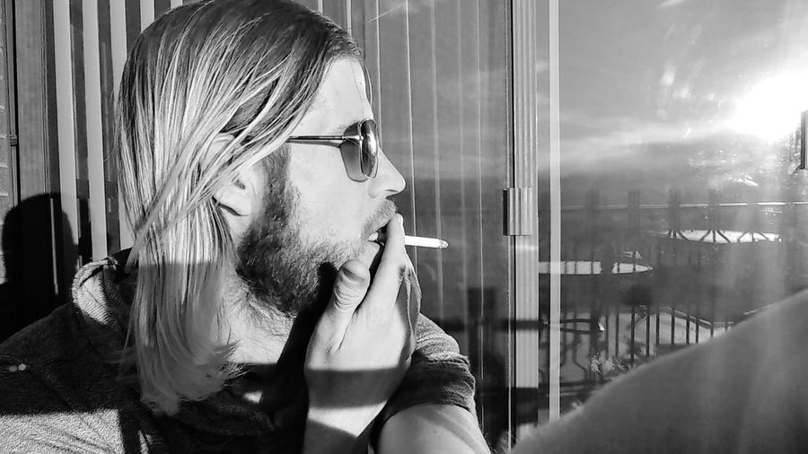 Close-Up Of Man Smoking Cigarette While Looking Through Window At Home