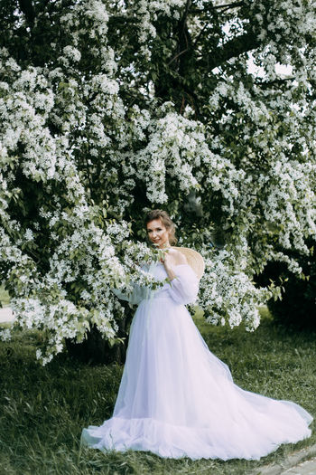 A beautiful delicate elegant woman bride in a wedding dress walks alone in a spring outdoor park