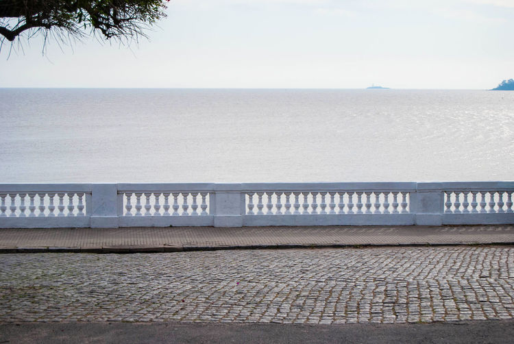 Old cobblestone street by the shore at Colonia del Sacramento, Uruguay. Water Sea Sky Railing Horizon Horizon Over Water Scenics - Nature Tranquil Scene Tranquility No People Beach Outdoors Built Structure Architecture Cobblestone Cobblestone Streets Antique Old Horizontal Copy Space