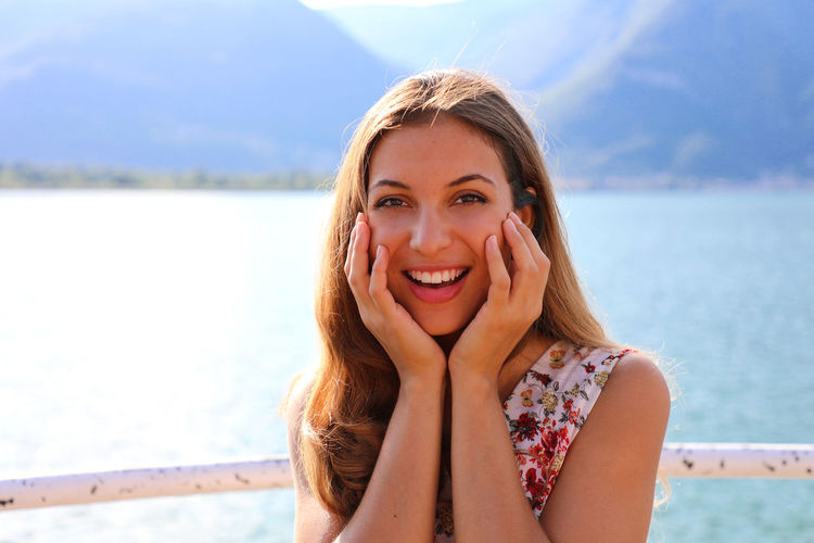 Portrait Of Smiling Young Woman Standing Against Mountains And Lake