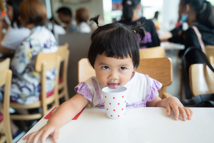 Cute girl licking cup while sitting at cafe