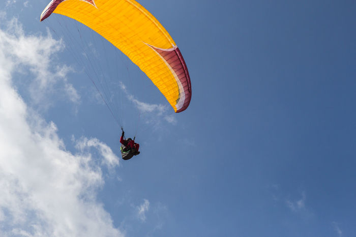 Adventure Blue Cloud - Sky Day Exhilaration Extreme Sports Flying Leisure Activity Lifestyles Low Angle View Men Mid-air Nature Outdoors Parachute Paragliding People Real People Sky Skydiving Sport Stunt Person Two People Unrecognizable Person