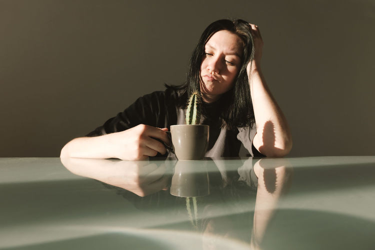 Young upset woman in a gray t-shirt holds in her hands a coffee cup with a cactus