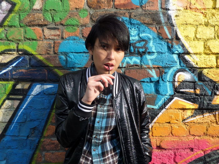 Portrait Of Serious Woman Against Graffiti Wall