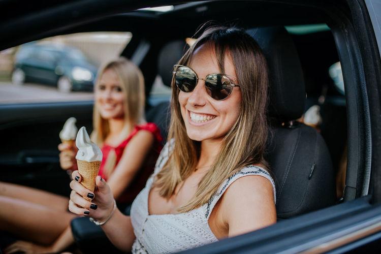 Woman wearing sunglasses sitting in car
