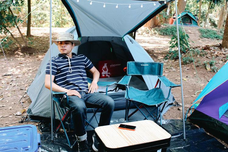 Full length of boy sitting in tent