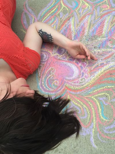 High angle view of woman lying by chalk drawing on street