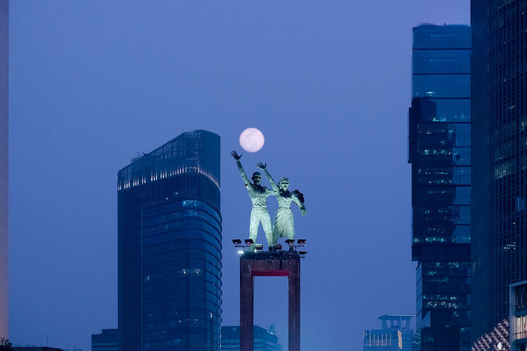 Architectural Column Architecture Blue Building Building Exterior Built Structure City Cityscape Clear Sky Financial District  Human Representation Modern Moonrise Nature No People Office Office Building Exterior Outdoors Representation Sculpture Sky Skyscraper Statue Supermoon Tall - High Travel Destinations