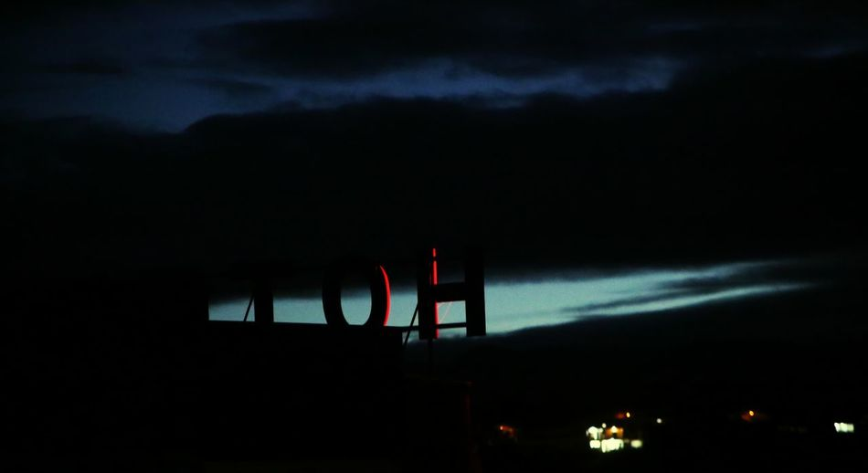 Low angle view of illuminated building against cloudy sky