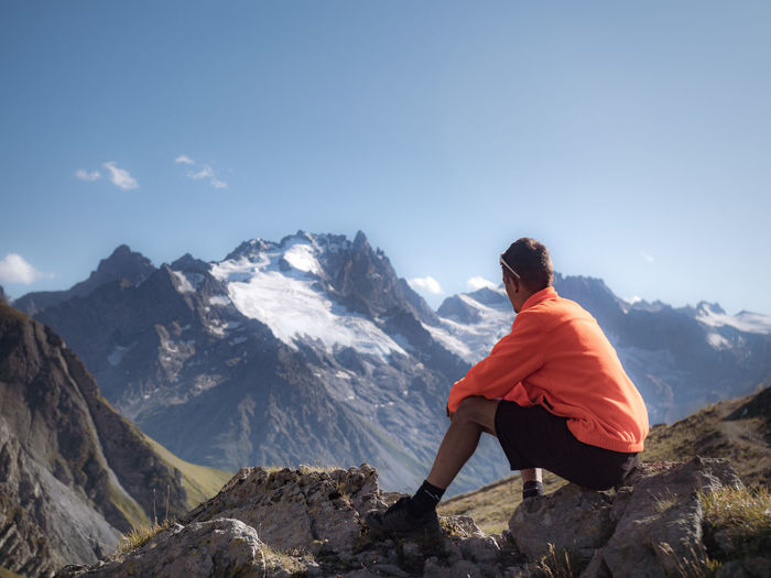 Man sitting on rock by mountains against sky