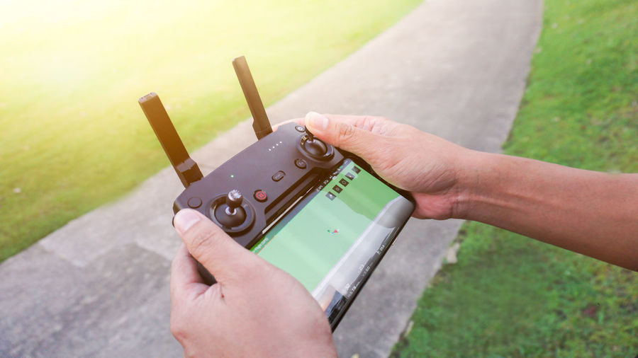 Drone  Control Finger Focus On Foreground Grass Hand Holding Human Body Part Human Finger Human Hand Outdoors Photography Themes Remote Technology