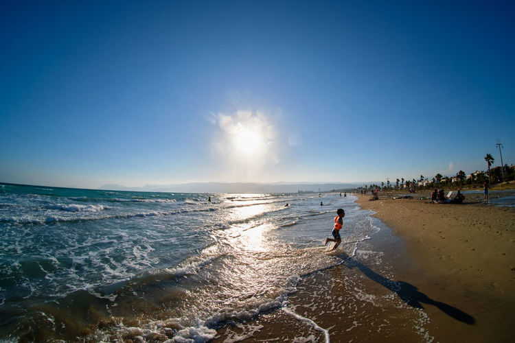 Unrecognizable boy with inflatable armbands runs out of sea to sandy beach. fish eye ultra wide shot