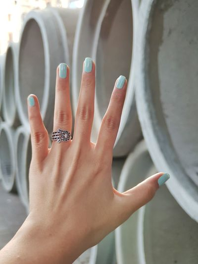 Cropped hand of woman showing painted fingernails