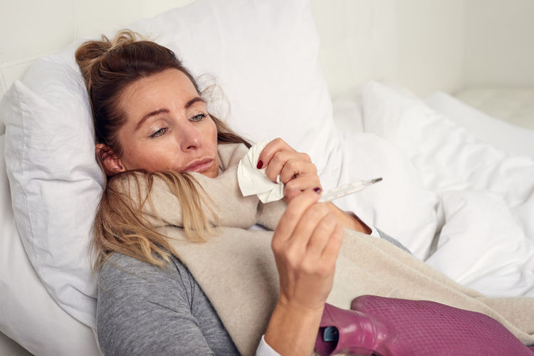 Sick woman taking her temperature Bed Copy Space FLU AND COLD SEASON Medicine Winter Woman Bedroom Best Ager Blond Cold Fever Flu Health Care Ill Middle-aged One Person Paper Tissue Seasonal Sick Sickness Thermometer