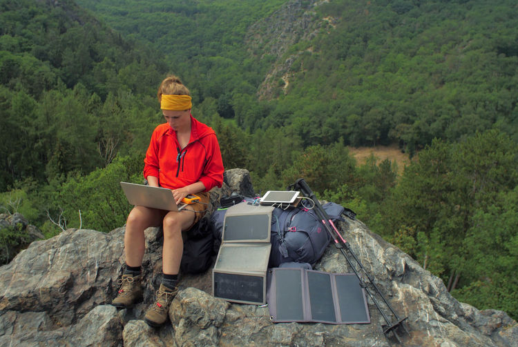 caucasian female hiker sitting on a rock while working on a laptop being charged by solar panels nearby, portable solar charing technology concept Backpacking Camping Charing Cross Freedom Hiking Nature Sitting Solar Panel Tablet Travel Trekking Woman Working Activity Adult Adventure Battery Casual Clothing Clothing Connection Day Female Forest Full Length Hiking Internet Laptop Leisure Activity Mountain Nature Navigation One Person Outdoors People Plant Portable Information Device Real People Sitting Technology Tree Young Adult