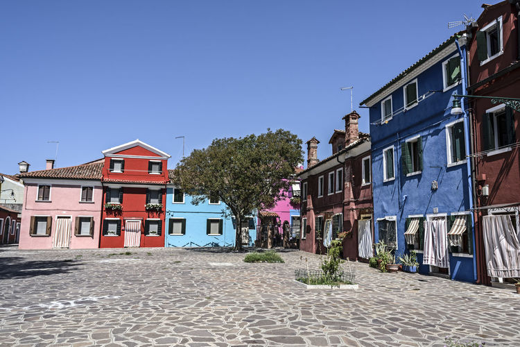 Houses by street in town against clear blue sky