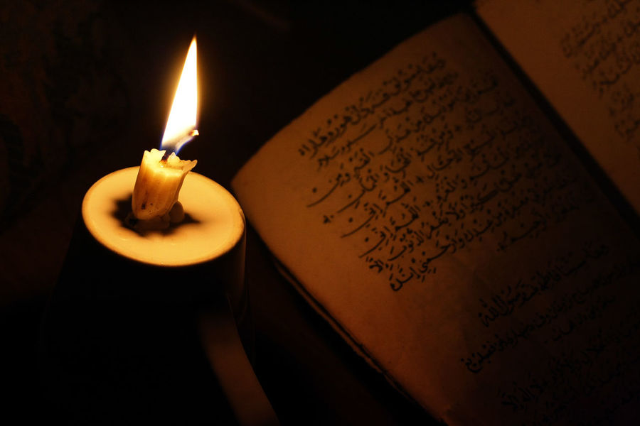 Recite n pray Arabic Reading Quran Recite The Holy Quran Recites And Pray Candle Light Flame Candle Burning Close-up Indoors