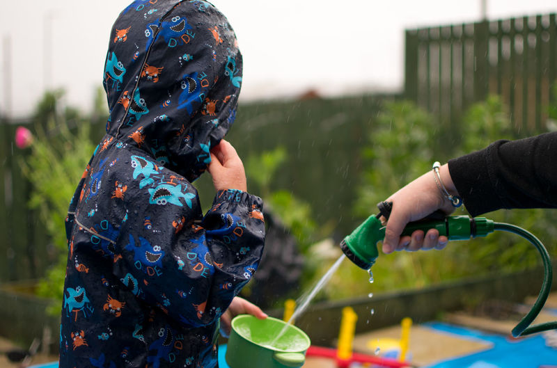 Cropped hand of person spraying water from hose in container held by child