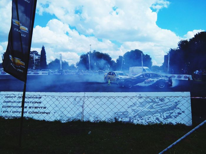 Cars drifting outside Cars Drifting Car Drifting EyeEmNewHere Blue Smoke Tyre Burning EyeEm Selects Pixelated City Sky Cloud - Sky