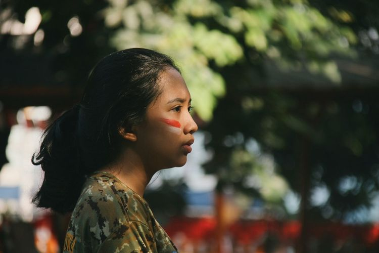 Profile view of woman with face paint against trees