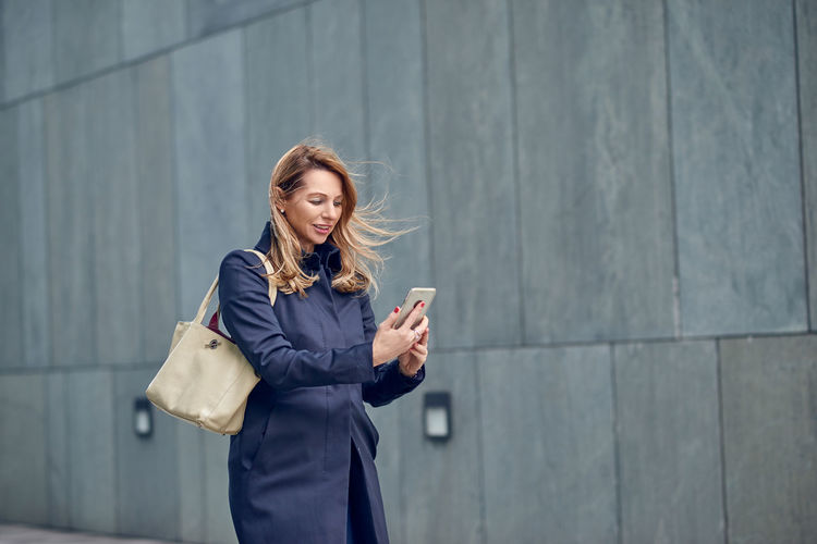 Middle-aged blond woman walking in the wind Architecture Blond Hair Businesswoman Coat Communication Hair Holding Middle-aged Mobile Phone One Person One Woman Only Outdoors Portable Information Device Real People Smart Phone Springtime Technology Walking Wall - Building Feature Wind Wireless Technology