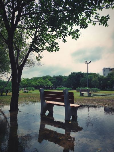Empty bench in park by lake against sky