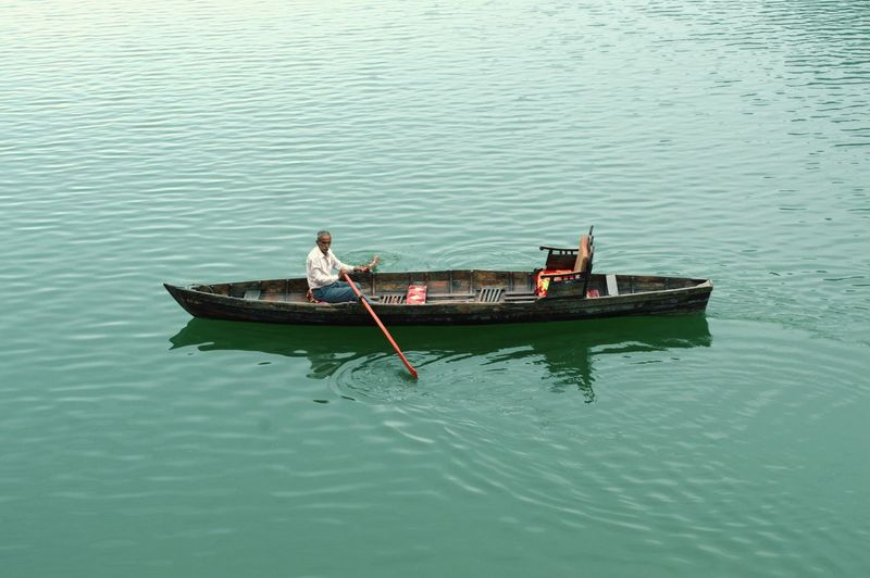 High Angle View Of Man Rowing Boat In Lake