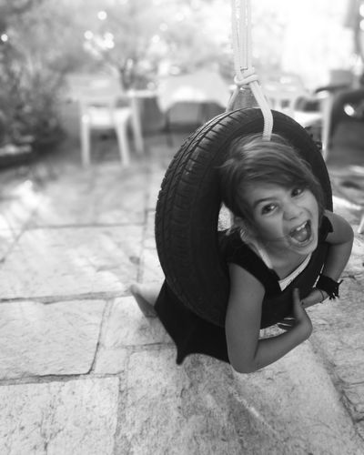 Portrait of girl screaming while swinging on tire