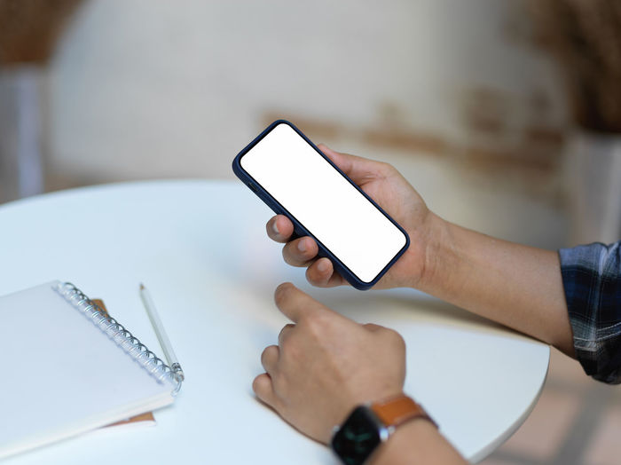 Cropped hand of man using mobile phone at office