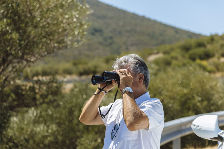 Photography Themes Activity Photographing One Person Technology Camera - Photographic Equipment Real People Leisure Activity Holding Waist Up Looking Through An Object Lifestyles Rear View Day Photographic Equipment Men Photographer Standing Nature Digital Camera Outdoors