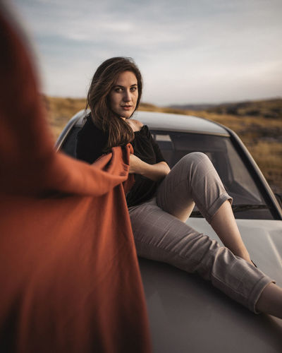 Portrait of woman sitting on top of a car against sky