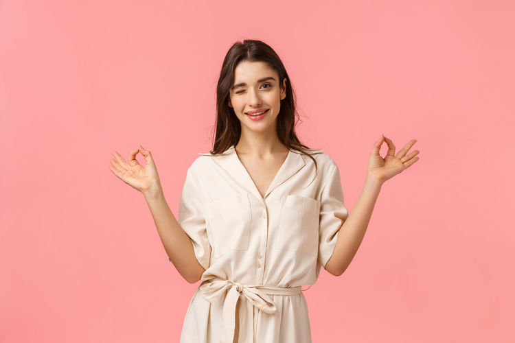 Portrait of smiling young woman against pink background