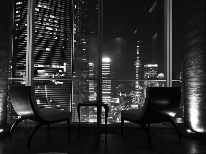 Empty Chairs By Window Against Illuminated Skyscrapers