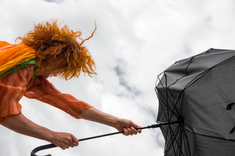 Woman holding umbrella while standing outdoors