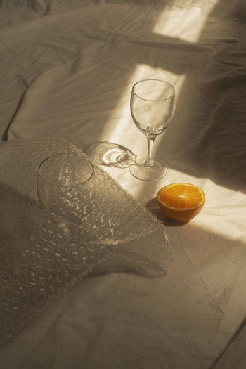 High angle view of wineglasses with orange fruit on table