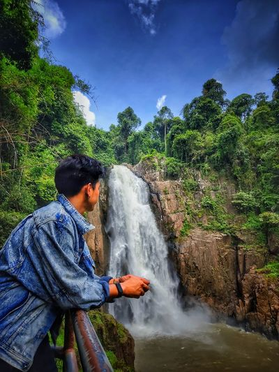Side view of man against waterfall