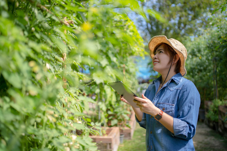 Young woman using phone while standing on plants