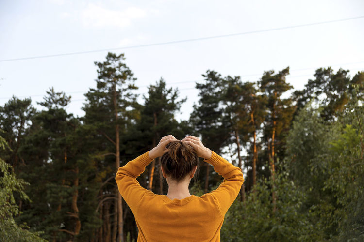 Rear view of woman standing by plants against sky