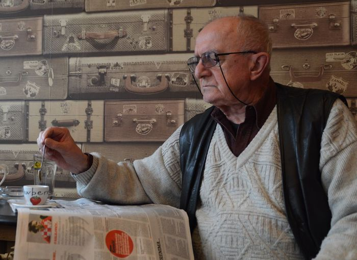 Senior Man Reading Newspaper While Stirring Coffee In Cafe