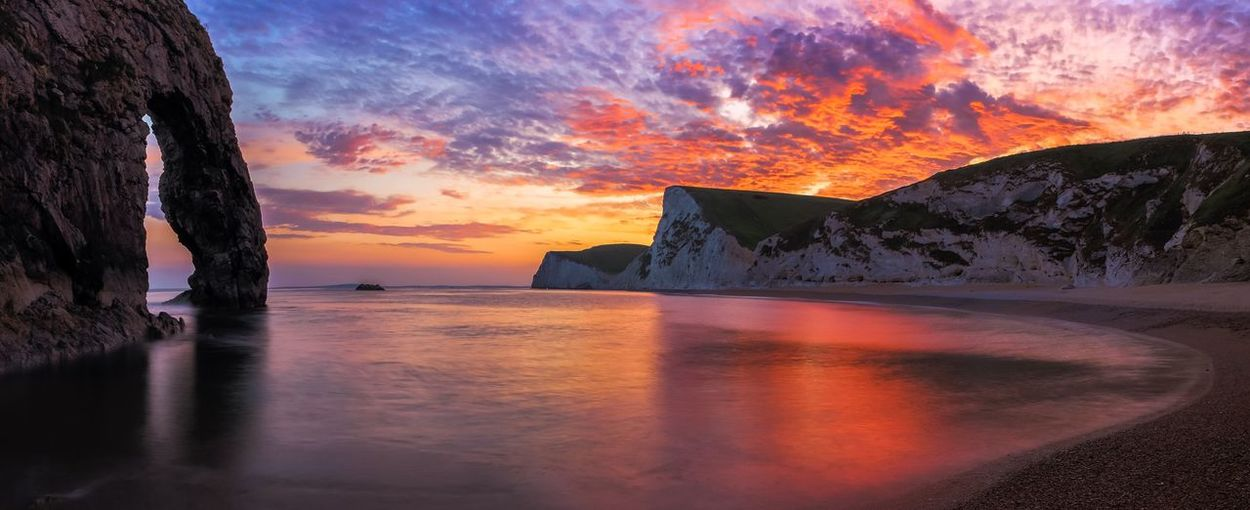 Durdle Door at dramatic sunset Durdle Door At Dramatic Sunset Dusk Natural Arch Limestone Arch Seaside Famous Place Water Reflections Nature Beauty Red Sky Marine Tranquility Bay Dorset Coastline Cliffs Colour Of Life Beach South Coast Purbeck The Great Outdoors - 2017 EyeEm Awards BYOPaper!