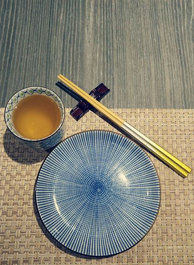 High Angle View Of Plate And Chopsticks By Green Tea On Table