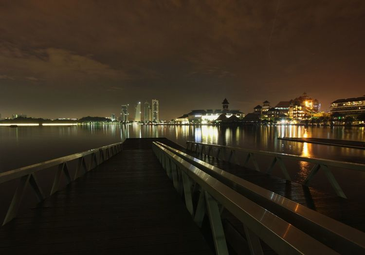 Pier over lake by illuminated city at night